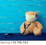 Teddy bear is sitting in a white medical mask, black stethoscope is... Стоковое фото, фотограф Zoonar.com/Danko Natalya / easy Fotostock / Фотобанк Лори