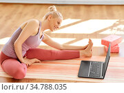 woman with laptop exercising at yoga studio. Стоковое фото, фотограф Syda Productions / Фотобанк Лори