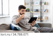 shocked man with tablet computer at home. Стоковое фото, фотограф Syda Productions / Фотобанк Лори