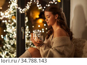 woman with christmas garland lights in glass mug. Стоковое фото, фотограф Syda Productions / Фотобанк Лори