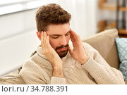 unhappy man suffering from head ache at home. Стоковое фото, фотограф Syda Productions / Фотобанк Лори