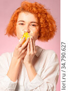 Fun pretty curly red hair girl eats sweet dessert on pink background. Стоковое фото, фотограф Zoonar.com/A.Tugolukov / easy Fotostock / Фотобанк Лори