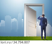 Businessman standing in front of door into future. Стоковое фото, фотограф Elnur / Фотобанк Лори