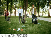 Young people collects trash in park, volunteering. Стоковое фото, фотограф Tryapitsyn Sergiy / Фотобанк Лори