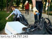 Volunteers picking trash in park, volunteering. Стоковое фото, фотограф Tryapitsyn Sergiy / Фотобанк Лори