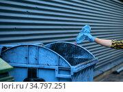 Volunteer puts trash into the can, volunteering. Стоковое фото, фотограф Tryapitsyn Sergiy / Фотобанк Лори