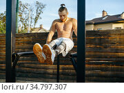 Muscular man doing abs exercise, street workout. Стоковое фото, фотограф Tryapitsyn Sergiy / Фотобанк Лори