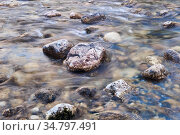 Natural background - stones in a rapid mountain stream, the water is blurred in motion. Стоковое фото, фотограф Евгений Харитонов / Фотобанк Лори