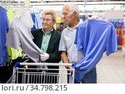 mature european couple chooses tee shirt in clothing department of supermarket. Стоковое фото, фотограф Татьяна Яцевич / Фотобанк Лори