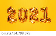 Happy New year 2021 celebration. Bright gold balloons figures, New Year Balloons on bright yellow background. Christmas celebration. Gold foil balloons numeral 2021 with 3d effect, VR concept. Стоковое фото, фотограф Сергей Тимофеев / Фотобанк Лори