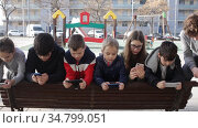 Group of children playing with smartphones outdoors at sunny spring day. Стоковое видео, видеограф Яков Филимонов / Фотобанк Лори