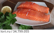 Raw seafood, fresh fillet salmon fish on wooden board. Стоковое видео, видеограф Яков Филимонов / Фотобанк Лори