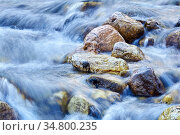 Cascade of waterfalls of a mountain river among the boulders, the water is blurred in motion. Стоковое фото, фотограф Евгений Харитонов / Фотобанк Лори