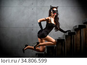 Sexy woman in catwoman suit lying on stairs at backyard of building. Стоковое фото, фотограф Zoonar.com/Figurniy Sergey / easy Fotostock / Фотобанк Лори