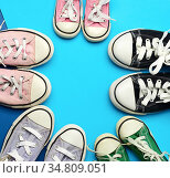Many multi-colored well-worn textile sneakers of different sizes on... Стоковое фото, фотограф Natalya Danko / easy Fotostock / Фотобанк Лори