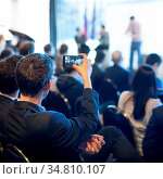 Businessman takes a picture of corporate business presentation at... Стоковое фото, фотограф Zoonar.com/Matej Kastelic / easy Fotostock / Фотобанк Лори