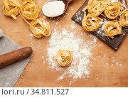 Raw fettuccine pasta on a brown wooden board and a wooden vintage... Стоковое фото, фотограф Zoonar.com/Danko Natalya / easy Fotostock / Фотобанк Лори