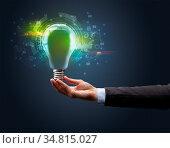 Hand holding light bulb on dark background. New business idea concept. Стоковое фото, фотограф Zoonar.com/rancz / easy Fotostock / Фотобанк Лори