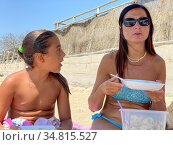 Woman with her daughter on the beach having fast food lunch. Vacation... Стоковое фото, фотограф Giovanni Gagliardi / easy Fotostock / Фотобанк Лори