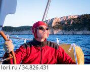 An experienced skipper steers the yacht peering into the distance. Стоковое фото, фотограф Сергей Фролов / Фотобанк Лори