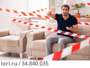 Young man feeling bored at home in self-isolation concept. Стоковое фото, фотограф Elnur / Фотобанк Лори