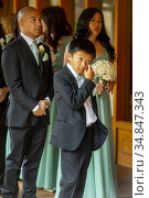 Carrying a bouquet, formally dressed multiracial wedding guests wait... Редакционное фото, фотограф Spencer Grant / age Fotostock / Фотобанк Лори