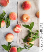 Several ripe juicy peaches on a gray background. Peach fruits on the wooden board. Green living. Organic food. Стоковое фото, фотограф Nataliia Zhekova / Фотобанк Лори