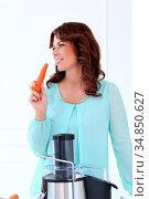 Vegetarian. Attractive woman with carrot. Стоковое фото, фотограф Zoonar.com/Yeko Photo Studio / easy Fotostock / Фотобанк Лори
