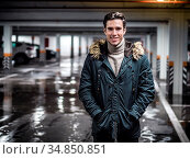 Young trendy man in winter outerwear standing in car parking and smiling... Стоковое фото, фотограф Zoonar.com/Stefano Cavoretto / easy Fotostock / Фотобанк Лори