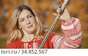 Feisty woman in red clothes standing on the field and posing with sword. Стоковое видео, видеограф Константин Шишкин / Фотобанк Лори