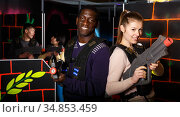Two laser tag players standing back to back. Стоковое фото, фотограф Яков Филимонов / Фотобанк Лори