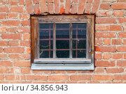 Old locked window with protective metal grate. Стоковое фото, фотограф EugeneSergeev / Фотобанк Лори