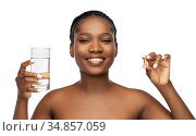african woman with cod liver oil and water glass. Стоковое фото, фотограф Syda Productions / Фотобанк Лори