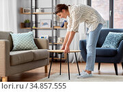 woman placing coffee table next to sofa at home. Стоковое фото, фотограф Syda Productions / Фотобанк Лори
