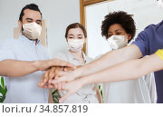 people in masks stacking hands at office. Стоковое фото, фотограф Syda Productions / Фотобанк Лори