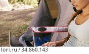 Woman using a laptop outside the tent. Стоковое видео, агентство Wavebreak Media / Фотобанк Лори