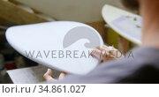 Man examining a surfboard 4k. Стоковое видео, агентство Wavebreak Media / Фотобанк Лори