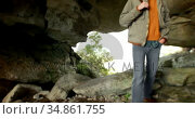 Male hiker standing with backpack in the cave 4k. Стоковое видео, агентство Wavebreak Media / Фотобанк Лори