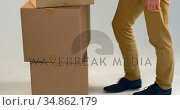 Man carrying stack of cardboard boxes against white background 4k. Стоковое видео, агентство Wavebreak Media / Фотобанк Лори