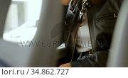Teenage girl talking on mobile phone while travelling in bus 4k. Стоковое видео, агентство Wavebreak Media / Фотобанк Лори