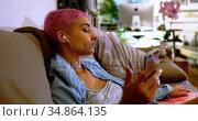 Pink hair woman using mobile phone on sofa 4k. Стоковое видео, агентство Wavebreak Media / Фотобанк Лори