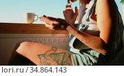 Woman sitting near window and using mobile phone 4k. Стоковое видео, агентство Wavebreak Media / Фотобанк Лори