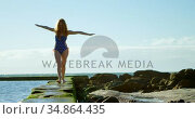 Woman walking with arms outstretched at beach 4k. Стоковое видео, агентство Wavebreak Media / Фотобанк Лори