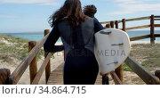 Surfer couple running with surfboard 4k. Стоковое видео, агентство Wavebreak Media / Фотобанк Лори