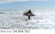 Woman with surfboard running on the sea 4k. Стоковое видео, агентство Wavebreak Media / Фотобанк Лори