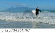 Man with surfboard running on the sea 4k. Стоковое видео, агентство Wavebreak Media / Фотобанк Лори