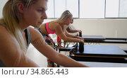 Women doing exercise with rowing machine 4k. Стоковое видео, агентство Wavebreak Media / Фотобанк Лори