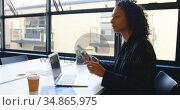 Businesswoman talking on mobile phone while using laptop 4k. Стоковое видео, агентство Wavebreak Media / Фотобанк Лори