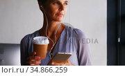 Businesswoman having coffee while listening music on mobile phone 4k. Стоковое видео, агентство Wavebreak Media / Фотобанк Лори