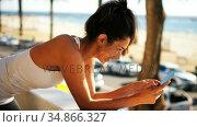 Woman using mobile phone in balcony 4k. Стоковое видео, агентство Wavebreak Media / Фотобанк Лори